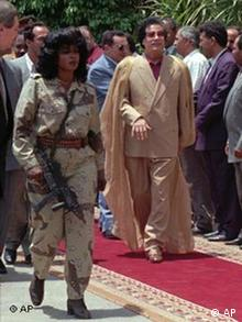 Libyan President Col. Moammar Gadhafi arrives at Qubba Palace in Cairo accompanied by one of his female bodyguards Saturday, May 25, 1996. Egyptian President Hosni Mubarak walks behind Gadhafi. The Libyan President is expected to stay in Egypt for at least three days. (AP Photo/Enric Marti)