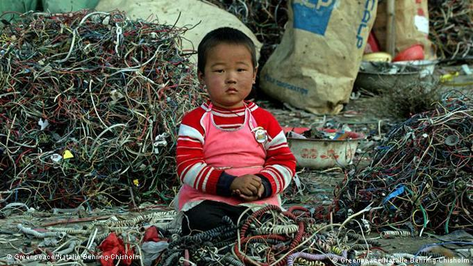 A child sits among cables and e-waste in Guiyu, China.