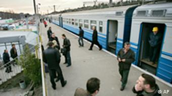 Ukrainian workers from Chernobyl power station wait to board a train to Chernobyl, at the railway station in the city of Slavutich, Monday, April 17, 2006. around 50,000 Pripyat residents were evacuated after the disaster, taking only few belongings. They never returned, workers and their families now live in a the new town of Slavutich, 30 km from the plant. the city was built following the evacuation of Pripyat, which was just 3 km away. On April 26, Ukraine will mark the 20th anniversary of the world's worst nuclear disaster. (AP Photo/Oded Balilty)