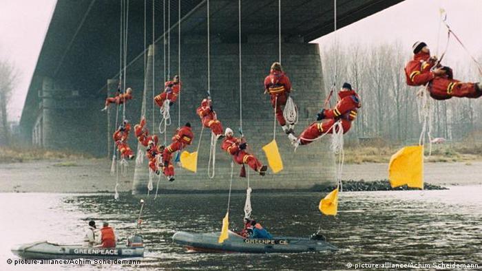 فعالین محیط زیست در سال ۱۹۸۶ با آویزان شدن از یک پل در شهر لورکوزن آلمان جلوی عبور کشتیهای حامل مواد شیمیایی کنسرن بایر را گرفتهاند.