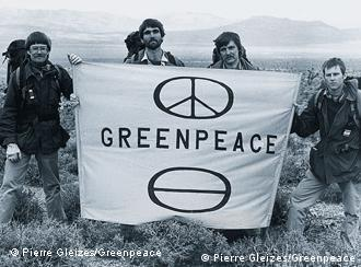 Black and white photo of the symbols of the peace movement and environmental protection on a banner held by activists