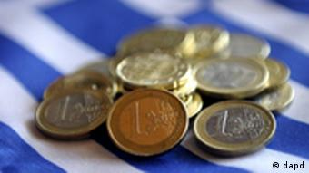 Euro coins piled on a Greek flag
