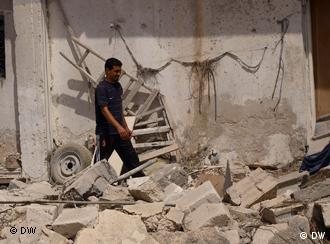 Libyan man in front of destroyed house