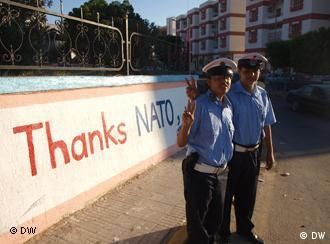 Police in Tropli stand in front of a sign that reads Thanks NATO
