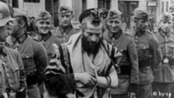 Єврей і німецькі солдати. На землі лежать долілиць інші євреї