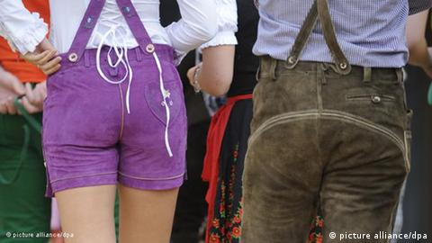 A woman and a man show off their lederhosen from the back (picture alliance/dpa)