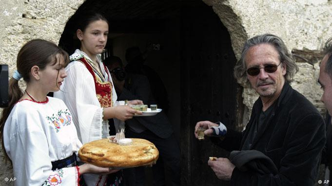 Austrian author Peter Handke, right, is offered bread, salt and home made brandyas he arrives in Serb Orthodox church of Sveti Stefan in the village of Velika Hoca, Saturday, April 7, 2007. Austrian author Peter Handke and the director of the Berlin Ensemble Theater Claus Peymann visited Kosovo on Saturday where they donated 50,000 euro to the people of a Serbian enclave Velica Hoca.(AP Photo/Visar Kryeziu)