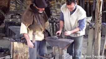 Workers in traditional garb at an anvil