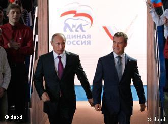 دمیتری مدودیف (راست) و ولادیمیر پوتین مقامهای خود را به عنوان رییسجمهور و نخستوزیر در کنفرانس حزب متحد روسیه با هم عوض کردند