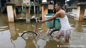 A man walks with his bicycle though a flooded street at a village along the Mekong River