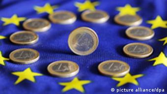 Euro coins arranged in a circle over the EU flag