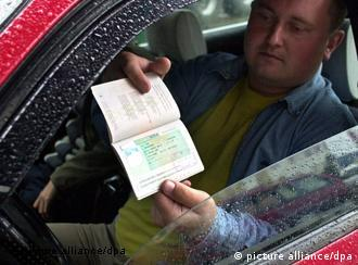 A man in a car showing his identification