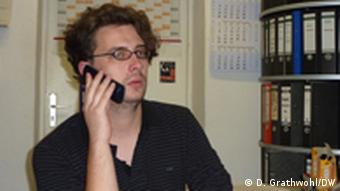 Jonas Thiele, chairman of the University of Cologne's student council, speaks on the phone
