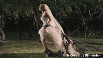 Bride in 'Melancholia' running away, with greenery in the background