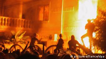 Bulgarian protesters stand in front of a house set on fire