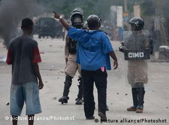 Residents scream at policemen during a protest against the United Nations Stabilization Mission in Haiti