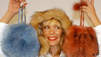 A woman in a fur-lined hat hold to fur-covered handbags