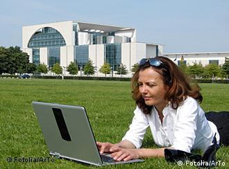 Frau mit Laptop liegt auf einer Wiese vor dem Kanzleramt in Berlin (Foto: Fotolia)