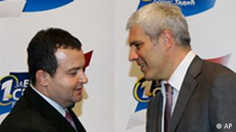 Kingmaker Dacic shakes hands with Tadic, right, at coalition talks in 2008