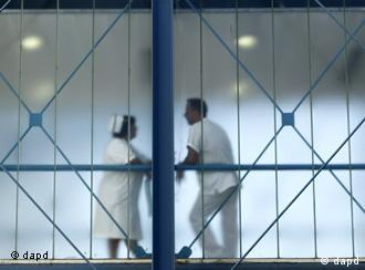 A nurse and another hospital staffer talk behind a glass skywalk