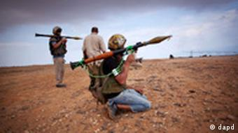Revolutionary fighters armed with rocket-propelled grenades take up positions in Sirte, Libya
