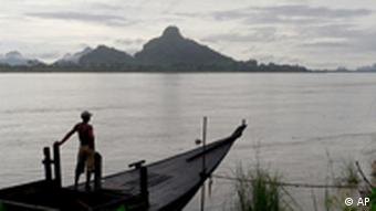 A man looks out from his boat on the bank of the Salween river in Myanmar