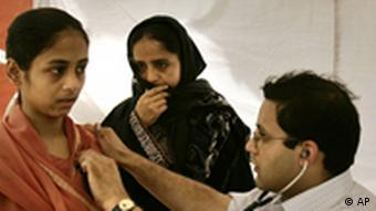 A doctor, right, checks a patient at a makeshift out patient's department set up on a pavement outside a hospital in New Delhi, India, Monday, May 15, 2006. Doctors at several private hospitals in the Indian capital only attended to emergency cases and stayed away from the outpatients department to express solidarity with their counterparts in government-run hospitals protesting an affirmative action program at medical and other professional colleges funded by the government. (AP Photo/Saurabh Das)