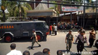Indonesian police officers stand guard after an apparent suicide bomb has exploded at the Kepunton church in Solo, Central Java