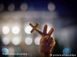 A hand holding up a cross and showing a victory sign