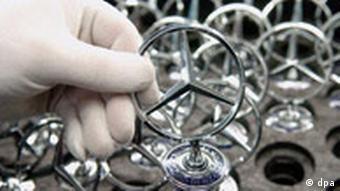 Ein DaimlerChrysler Mitarbeiter hält im Mercedes-Werk in Sindelfingen (bei Stuttgart) am Mittwoch (09.02.2005) mit weißen Handschuhen einen Mercedes Stern in der Hand