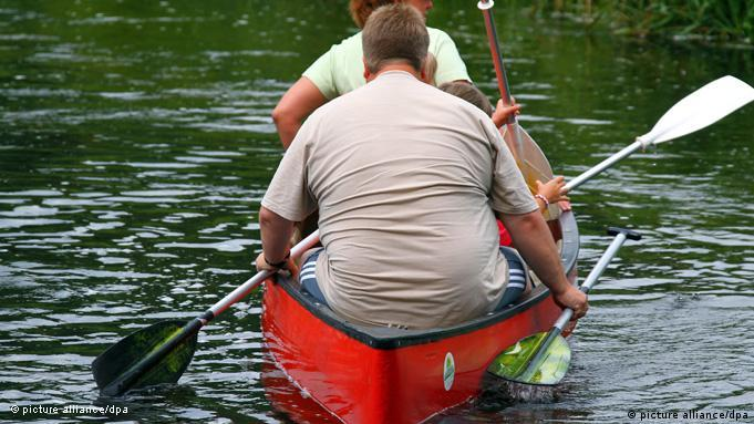 An overweight man in a canoe