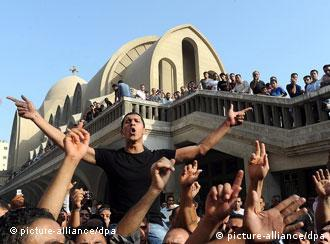 Egyptian Coptic Christians shout slogans and hold crosses