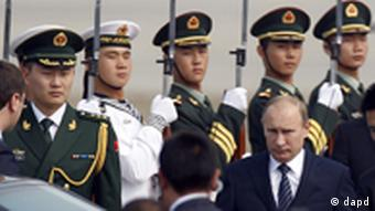 Russian Prime Minister Vladimir Putin, walks past a Chinese Guard of Honor contingent upon arriving by plane to the airport in Beijing, China