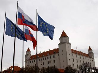 Flags of Slovakia and the European Union blow in the wind in front of the Parliament building, not seen, prior to a vote for approval for more power to EU rescue funds in Bratislava, Slovakia, Tuesday, Oct. 11, 2011. Bratislava Castle is on the background. (Foto:Petr David Josek/AP/dapd)