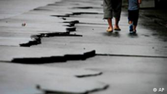 A father and son walk by cracks following a 6.5-magnitude earthquake at Yaizu port in Shizuoka Prefecture (State), Japan, Tuesday, Aug. 11, 2009. The quake hit Tokyo and nearby areas shortly after dawn Tuesday, halting trains and forcing two nuclear reactors to shut down for safety checks. (AP Photo/Itsuo Inouye)