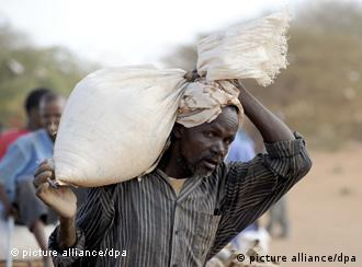 A Somalian refugee carries a sack of wheat provided by the WFP in a refugee camp in Dadaab, northeastern Kenya on thursday, August 4, 2011. Somalia and parts of Kenya have been struck by one of the worst draughts and famines in six decades, more than 350.000 refugees have found shelter in the worlds biggest refugee camp. Photo: Boris Roessler dpa +++(c) dpa - Bildfunk+++
