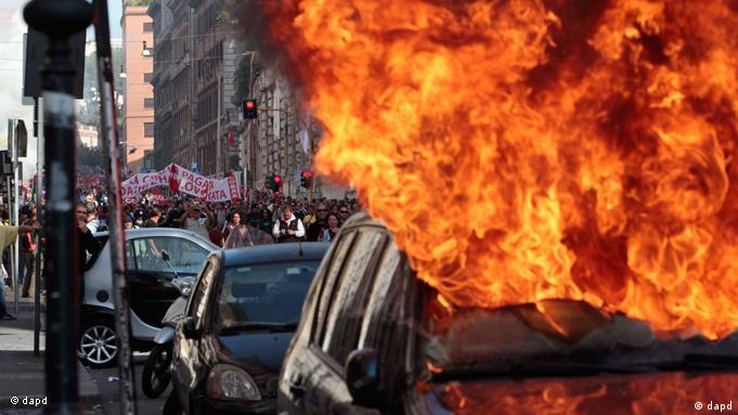 A car is set on fire as protesters clash with police in Rome, Saturday, Oct. 15, 2011. Protesters in Rome smashed shop windows and torched cars as violence broke out during a demonstration in the Italian capital, part of worldwide protests against corporate greed and austerity measures. The Occupy Wall Street protests, that began in Canada and spread to cities across the U.S., moved Saturday to Asia and Europe, linking up with anti-austerity demonstrations that have raged across the debt-ridden continent for months. (Foto:Gregorio Borgia/AP/dapd)