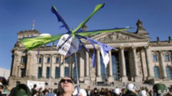 Ein Demonstrant mit einem kaputten 'Rettungsschirm' vor dem Bundestag in Berlin (Foto: AP)