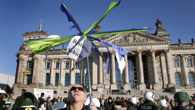 A man holds a broken umbrella in front of the Reichstag building in Berlin, Germany, Saturday, Oct. 15, 2011 during a demonstration to support the 'Occupy Wall Street' movement. Protestors gathered at many major European cities Saturday to join in demonstrations against corporate greed and inequality. (AP Photo/Michael Sohn)