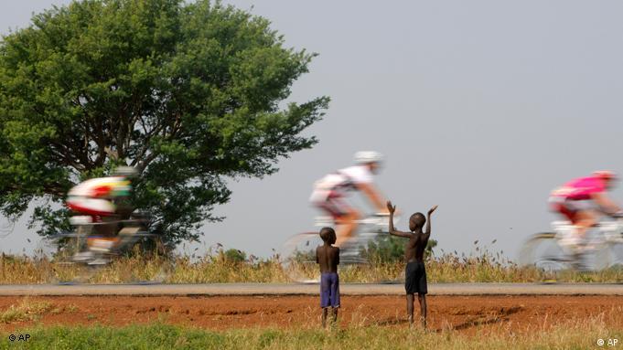Kinder blicken auf die Tour du Faso 2008. (Foto: AP)