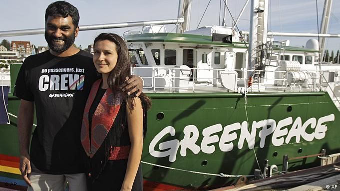 Naidoo standing with his arm around Laboucan's shoulder, with the green and white boat marked 'Greenpeace' in the background