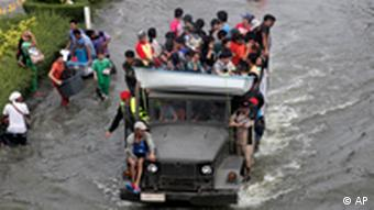 Thai people ride on a military truck to wade through floodwaters in Nonthaburi province, north of Bangkok, Thailand, Thursday, Oct. 20, 2011. Thailand's new premier acknowledged the country's flood crisis has overwhelmed her government, pleading for mercy from the media and solidarity from the country in battling the relentless waters. (AP Photo/Sakchai Lalit)