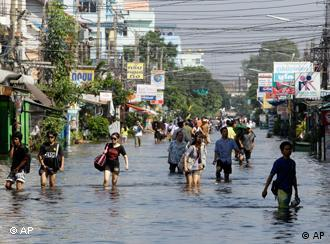 Thai people wade through a flooded area in Phatum Thani Province, north of Bangkok ,Thailand, Wednesday, Oct. 19, 2011. Thai authorities were staging a fighting retreat Wednesday against flood waters that threaten Bangkok, after the country's oldest factory park was completely inundated and a nearby one faced imminent threat. (AP Photo/Sakchai Lalit)