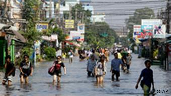 People wade through a flooded area in Bangkok