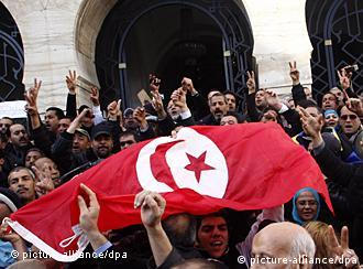 epa02623358 Tunisians stand hold a Tunisian national flag as they celebrate the dissolution of the former ruling party Constitutional Democratic Rally (RCD) by a Tunisian court, in front of the justice Place in Tunis, Tunisia, 09 March 2011. The party had been suspended from official activities in February 2011 by the interior ministry after former president Ben Ali fled abroad on January 14 at the height of a popular uprising to overthrow his autocratic regime. EPA/STRINGER +++(c) dpa - Bildfunk+++