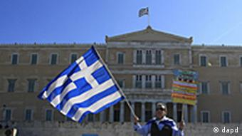 A protester wrapped with a Greek flag
