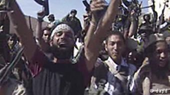 Libyan fighters celebrate in the streets of Sirte Libya in this image taken from TV Thursday Oct. 20, 2011. The Libyan fighters on Thursday overran the remaining positions of Moammar Gadhafi loyalists in his hometown of Sirte, ending the last major resistance by former regime supporters still holding out two months after the fall of the capital Tripoli. (Foto:APTN/AP/dapd) TV OUT