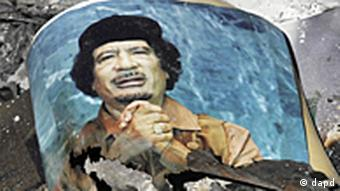 picture of Libya's ousted leader Moammar Gadhafi is seen in the ashes in downtown Sirte, Libya