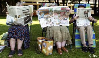 Drei ältere Herrschaften sitzen Zeitungen lesend im Liegestuhl