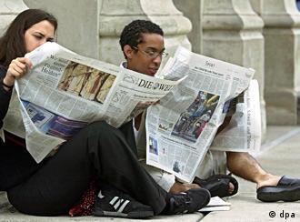 Paar liest auf dem Boden sitzend eine deutsche Tageszeitung